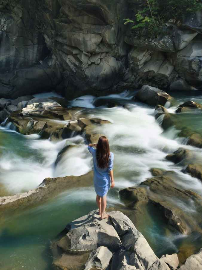 woman in blue long sleeved dress standing in middle of rock with raging water
